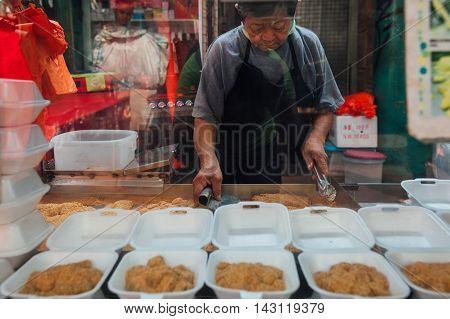 KUALA LUMPUR MALAYSIA - MARCH 17: Famous madam Tang sells Muah Chee desert at Petaling street Chinatown on March 17 2016 in Kuala Lumpur Malaysia