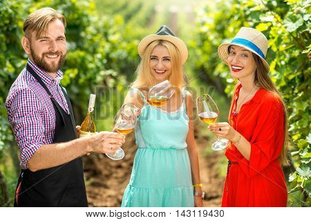 Handsome wine maker tasting wine with two women in colorful dresses on the vineyard. Wine degustation outdoors on the plantaion