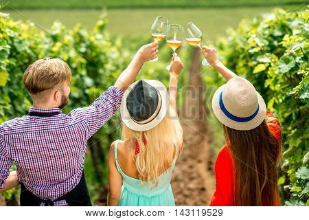 Young people looking at the wine glasses standing back on the vineyard during the wine degustation. Rear view focused the hats