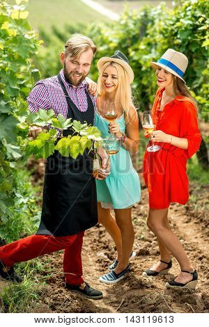 Wine maker showing grapes to women on the vineyard