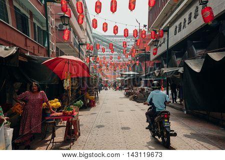 KUALA LUMPUR MALAYSIA - MARCH 17: Man riding motorbike through the crowded Petaling street Chinatown on March 17 2016 in Kuala Lumpur Malaysia