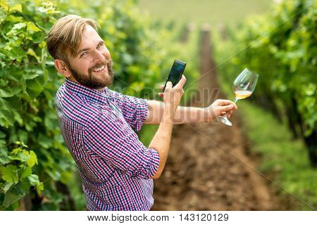 Wine maker or winery owner photographing glass of wine on the vineyard. Promoting wine in social networks