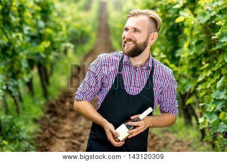 Portrait of handsome wine maker in apron with bottle of white wine standing on the vineyard
