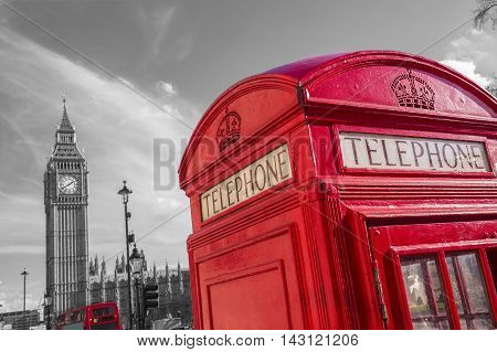 Famous British red telephone box with Big Ben and Double Decker bus at background on a sunny day -black and white version - London, UK