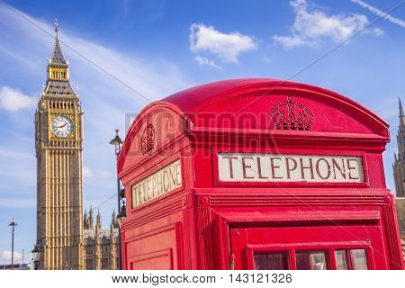 London, UK - Iconic British red telephone box with Big Ben and Double Decker bus at background on a sunny day with blue sky
