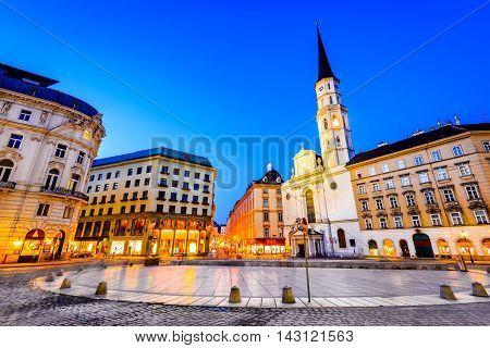 Vienna Austria. Michaelerplatz wide-angle view at dusk with Michaelkirche Habsburg Empire landmark in Wien