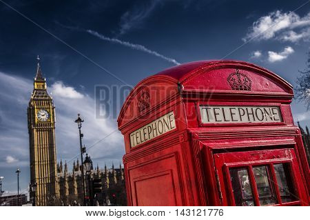 London, UK - Traditional British red telephone box with Big Ben on a sunny day with dark blue sky