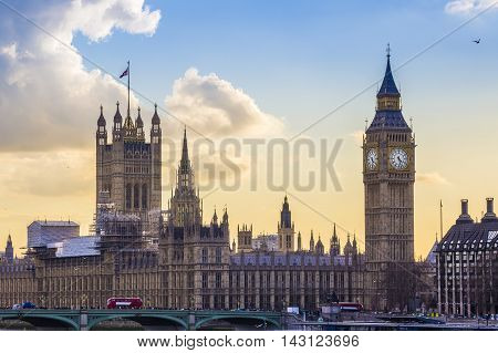 London, England - The famous Big Ben and Houses of Parliament with Westminster Bridge and Red Double Decker bus at sunset