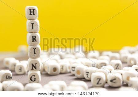 HIRING word written on wood block. Wooden Abc.