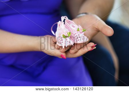 Pregnant Woman And Her Husband Holding Baby Shoes On Her Hands