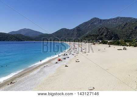 OLUDENIZ TURKEY - JUNE 04: Tourists visit Oludeniz beach in Turkey on JUNE 04 2016. Oludeniz beach is one of the best beaches in Turkey it's situated on Mediterranean Sea