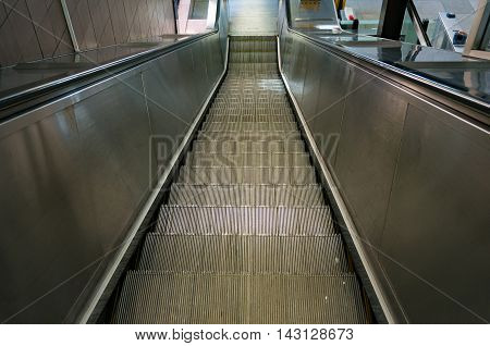 Steel escalator going downstairs. View from human height poster