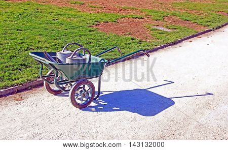 Drought: two watering cans in a wheelbarrow