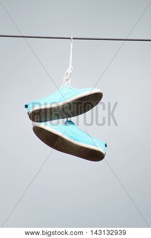 A pair of used light blue snicker shoes with white dirty soles and white shoelaces hanging by the shoelaces on a high wire on a gray sky background.