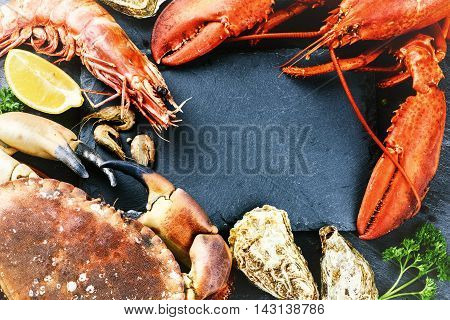 Food frame with crustacean for dinner. Lobster crab jumbo shrimps and oysters on dark background