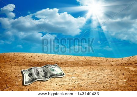 conceptual image of money on dried and cracked landscape
