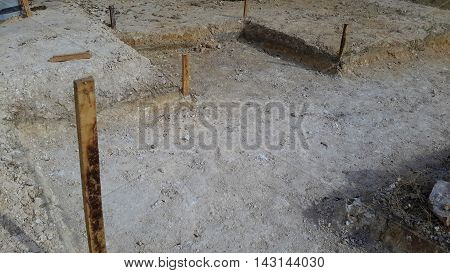 shallow foundation excavation, with wooden stakes at the corners, pile of paving stones on the right, Songkhla, Thailand