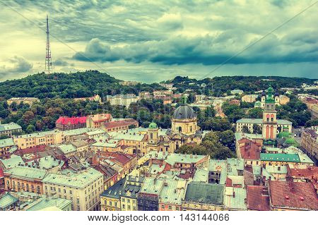 Lviv Ukraine old city vintage toned top view panorama with houses roofs. High Castle park Dominican Church Korniakt Tower Dormition Assumption church television tower