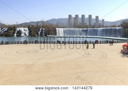 Kunming China - March 4 2016: Tourists wisiting the Kunming Waterfall park featuring a 400 meter wide manmade waterfall. Kunming is Yunnan's capital