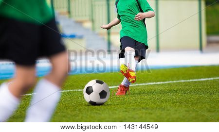 Football soccer kick. Young player kicking soccer ball