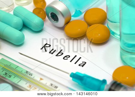 Rubella - diagnosis written on a white piece of paper. Syringe and vaccine with drugs.