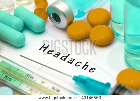 Headache - diagnosis written on a white piece of paper. Syringe and vaccine with drugs.