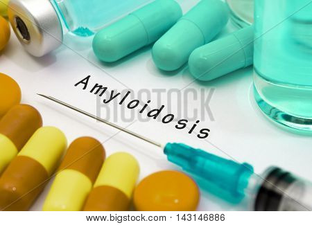 Amyloidosis - diagnosis written on a white piece of paper. Syringe and vaccine with drugs.