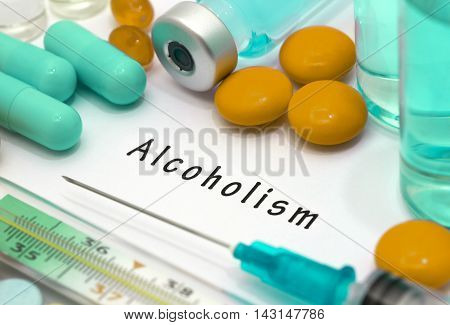 Alcoholism - diagnosis written on a white piece of paper. Syringe and vaccine with drugs.