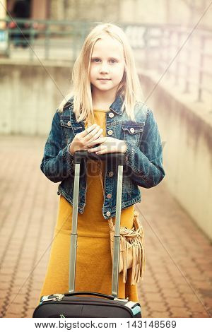 Young girl with light hair travelling with small laggage