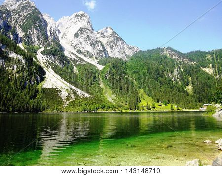 View Idyllic, beauty alpine landscape in Austria: lake, mountains, green grass, blue sky. Beautiful view on the Lake Gosau and Austrian Alps, Salzkammergut region, Upper Austria, Austria, Europe