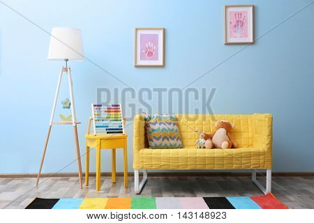 Yellow sofa with toys in children room