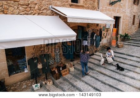 Pollensa Mallorca Spain - May 24 2015: Stores and souvenir shops with the seller and the buyer on the steps of the stairway to the Calvary church from the center of Pollensa Mallorca.
