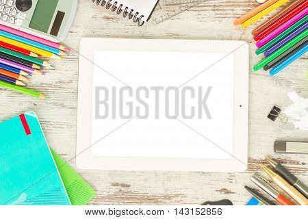 back to school frame with school supplies and tablet with empty screen on wooden table