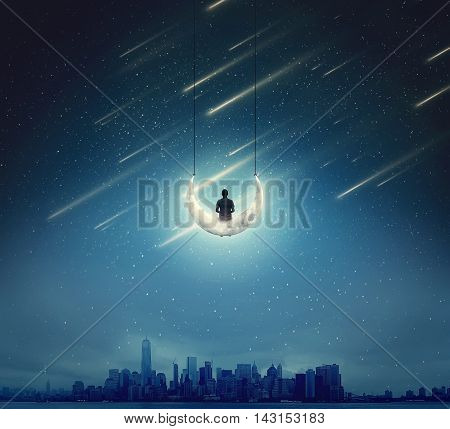 Surreal background with a boy sitting on a crescent moon as a swing over a big city in a starry night