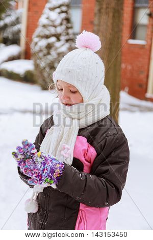 cute little girl is going skate outdoors beautiful little girl playing with snow