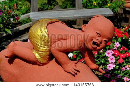 Chiang Mai Thailand - December 21 2012: Delightful terra cotta statue of a young monk in the gardens at Wat Tha Ka Rong