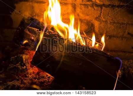 Slowly burning firewoods in a fireplace in a dark red-orange background.