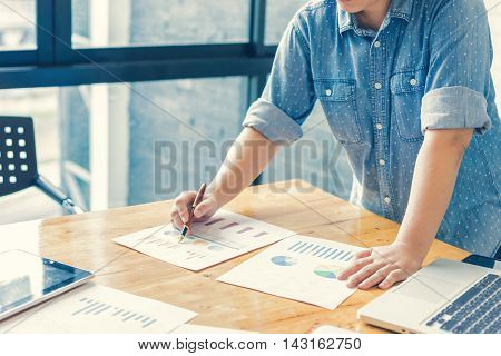 Businesswoman analyzing investment charts. Accounting with soft focus vintage tone