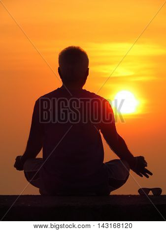 A man meditating against the setting sun a spiritual retreat during the summer holidays