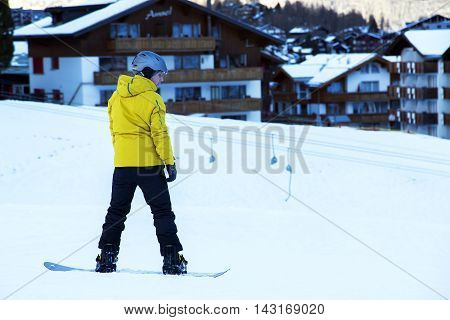 SWITZERLAND, SAAS-FEE, DECEMBER, 26, 2015 - Young man with ski suit practicing snowboarding on background  t-bar while skiing at Saas-Fee, Switzerland.