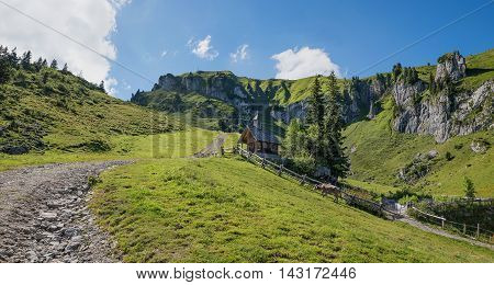 Pictorial Mountain Scenery With Wooden Chapel And Milker, Upper Bavaria