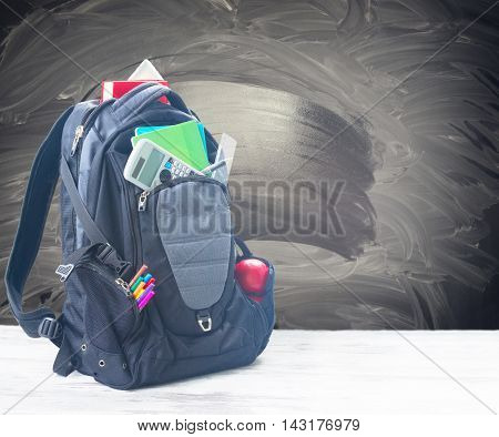 School backpack with supplies on white desktop with empty blackboard in background
