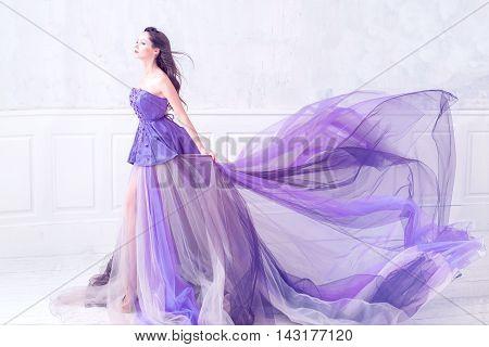 Beautiful brunette woman wearing long purple dress posing in empty light interior