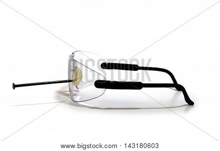 Side view of safety goggles with a nail stuck in the lens.