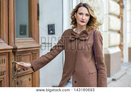 Pretty middleaged woman in jacket opens old door, shallow dof