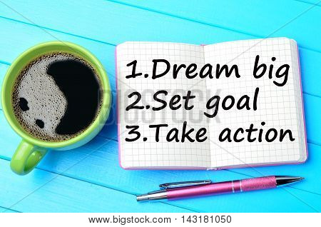Text Dream big Set goal Take action on notepad