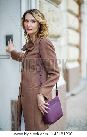 Beautiful middleaged woman in jacket rings the door speakerphone, shallow dof