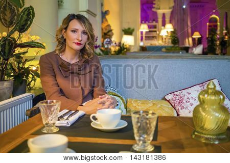 Middleaged blonde woman sits on couch with tea and looks at camera in restaurant