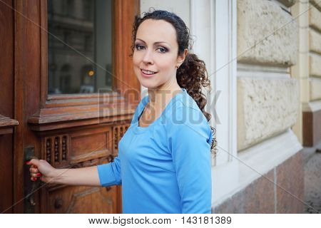 Pretty smiling woman in blue dress opens wooden door outdoor, shallow dof