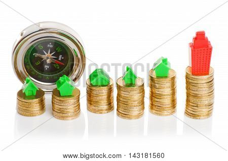 Stacks of coins, green and red home with compass. Mortgage concept by money house from coins poster